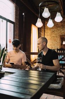 Beaux jeunes hommes en vêtements décontractés en regardant leurs smartphones