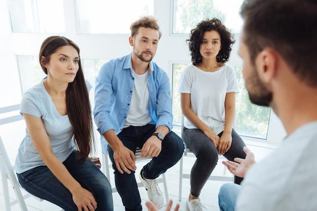 Beaux jeunes malheureux regardant leur thérapeute et écoutant le sien tout en visitant une session de groupe