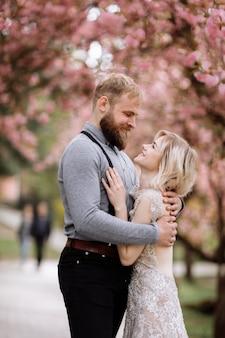 De beaux jeunes mariés s'étreignent et sourient contre la fleur de cerisier rose en fleurs par une journée ensoleillée. close-up de portrait de mariage de printemps du marié et jolie blonde mariée.