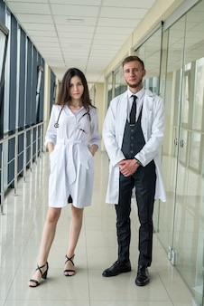 De beaux jeunes médecins regardent la caméra en clinique. concept de soins de santé et médical