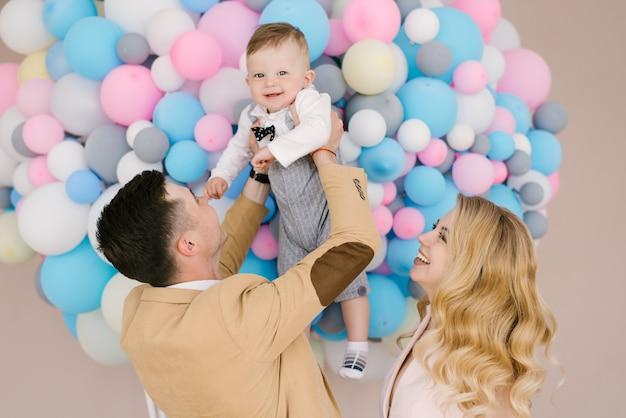 De beaux jeunes parents sourient avec leur enfant d'un an sur des ballons roses et bleus. look familial. joyeux anniversaire