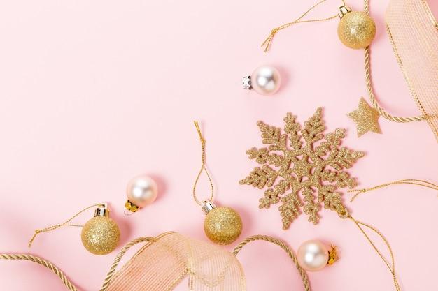 Beaux jouets décoratifs de noël étincelants dorés sur fond rose pastel.