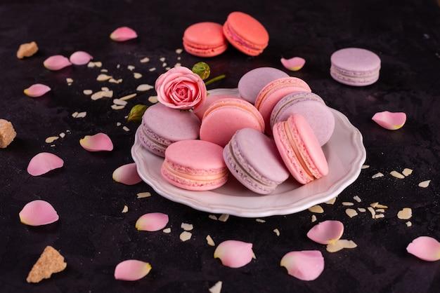 Beaux macarons roses savoureux sur un fond de béton
