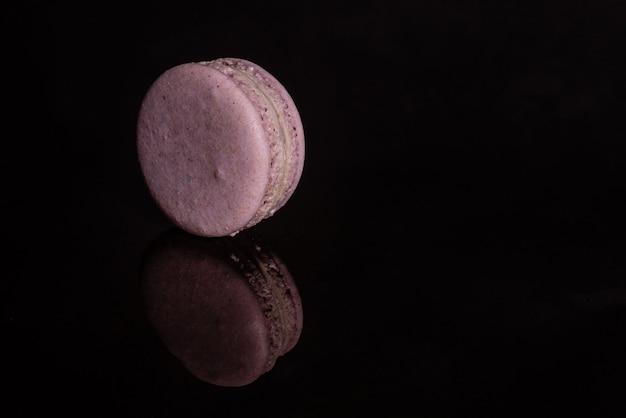 Beaux macarons roses savoureux sur un fond sombre