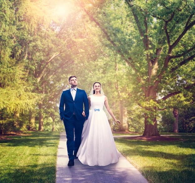 Beaux mariés marchant dans un parc verdoyant.