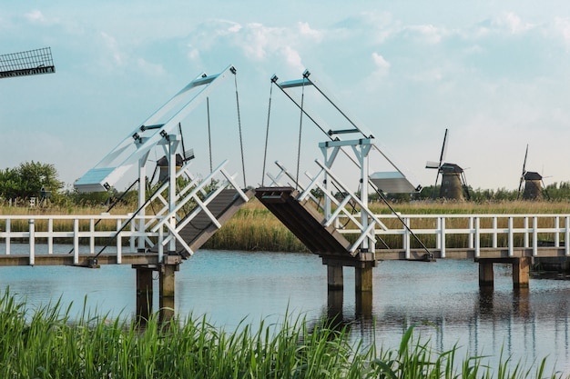 Beaux moulins à vent hollandais traditionnels près des canaux d'eau avec pont-levis