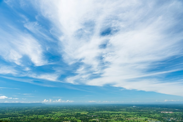 Beaux nuages duveteux avec terre d'herbe verte ou paysage de terrain d'herbe verte.