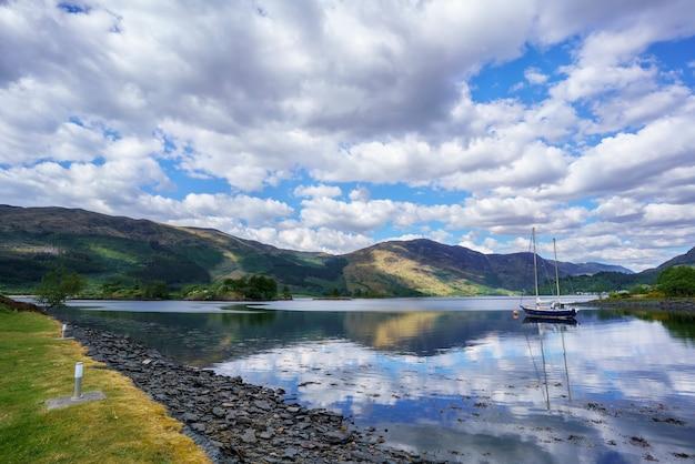 Beaux paysages du loch leven avec vue sur eilean munde ou l'île funéraire avec une chaîne de montagnes spectaculaire, des nuages et un reflet du ciel bleu à glencoe, en écosse
