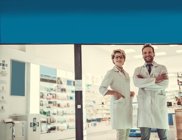 De beaux pharmaciens regardent la caméra.