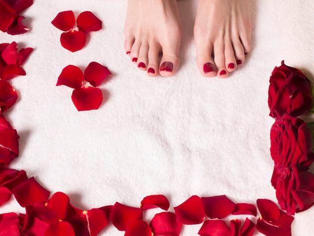 Beaux pieds féminins avec une belle pédicure sur une serviette éponge aux pétales de rose. concept de spa et de soins de la peau.