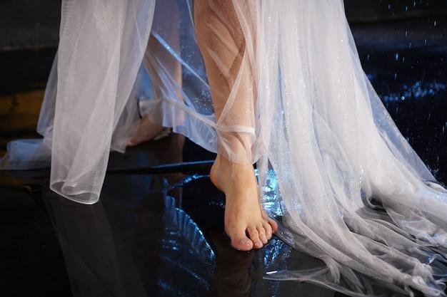 Beaux pieds féminins dans l'eau avec des éclaboussures. photo dans un néon en studio. voile blanc ou robe longue