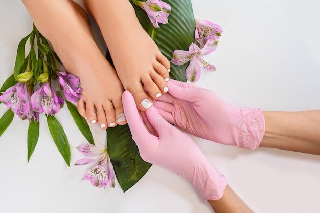 Beaux pieds féminins parfaits vue de dessus avec des fleurs tropicales et des feuilles de palmier vert