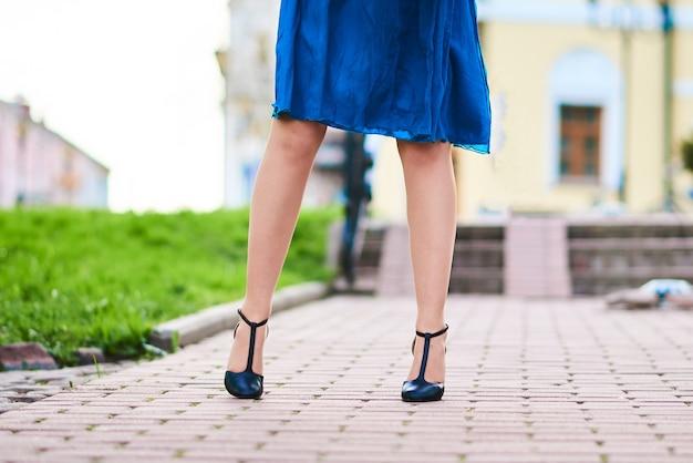 Beaux pieds de femmes en chaussures et robe