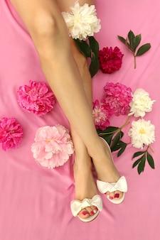 Beaux pieds de femmes avec des pivoines en sandales blanches et avec une pédicure multicolore sur les ongles.