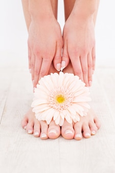 Beaux pieds. gros plan d'une jeune femme touchant ses pieds en se tenant debout sur un plancher de bois franc