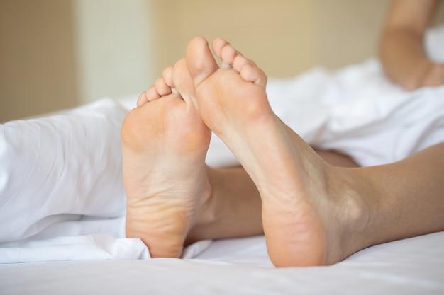Beaux pieds d'une jeune femme allongée dans son lit se bouchent