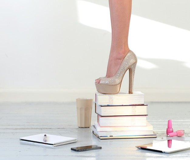 Beaux pieds sur des livres empilés
