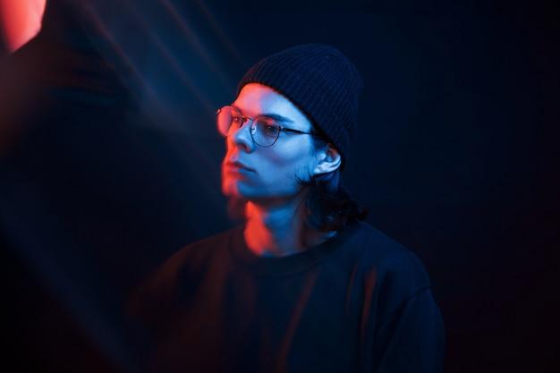 Beaux reflets. studio tourné en studio sombre avec néon. portrait d'homme sérieux