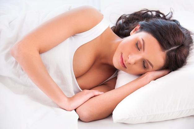 Beaux rêves. belle jeune femme allongée dans son lit et gardant les yeux fermés tout en étant recouverte d'une couverture