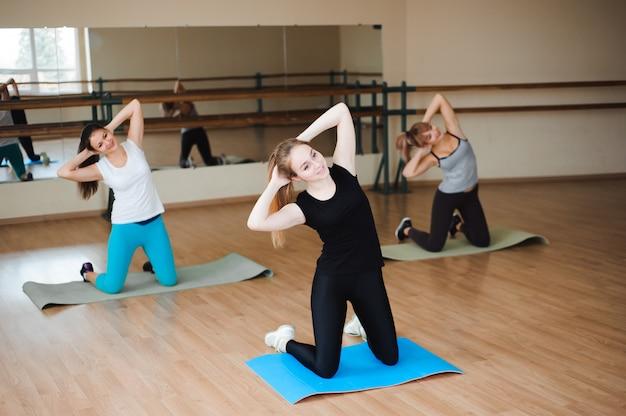 De beaux sportifs font des exercices et sourient tout en travaillant dans la salle de gym