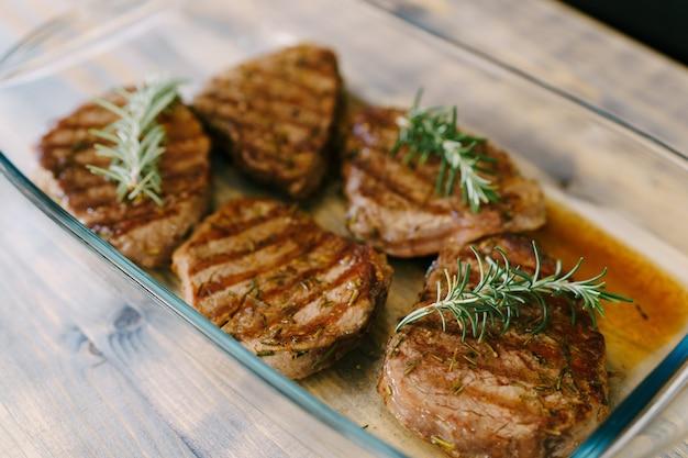 Beaux steaks grillés dans une assiette en verre sur une surface en bois dans leur propre jus et brins de