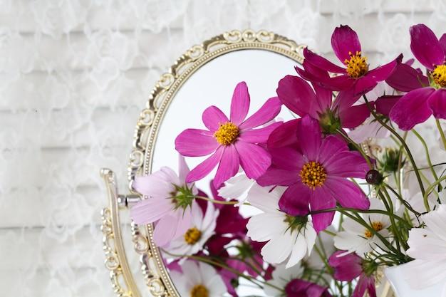 Beaux vases design avec des fleurs sur une table avec un miroir