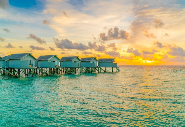 Beaux villas d'eau dans l'île des maldives tropicales au coucher du soleil