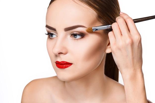 Beaux yeux féminins avec maquillage bleu vif et pinceau sur blanc