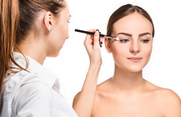 Beaux yeux féminins avec maquillage et pinceau sur blanc. processus de travail du maquilleur