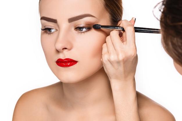 Beaux yeux féminins avec maquillage et pinceau sur blanc