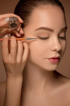 Beaux yeux féminins avec maquillage et pinceau