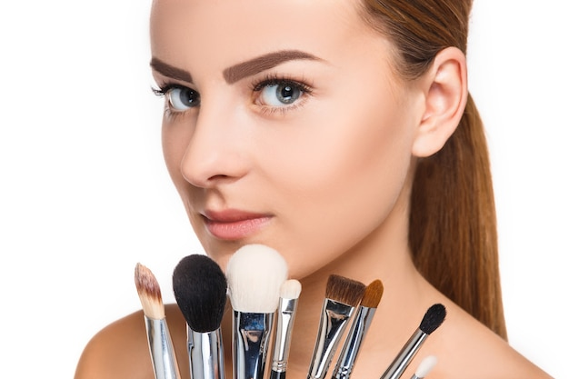 Beaux yeux féminins avec maquillage et pinceaux sur blanc