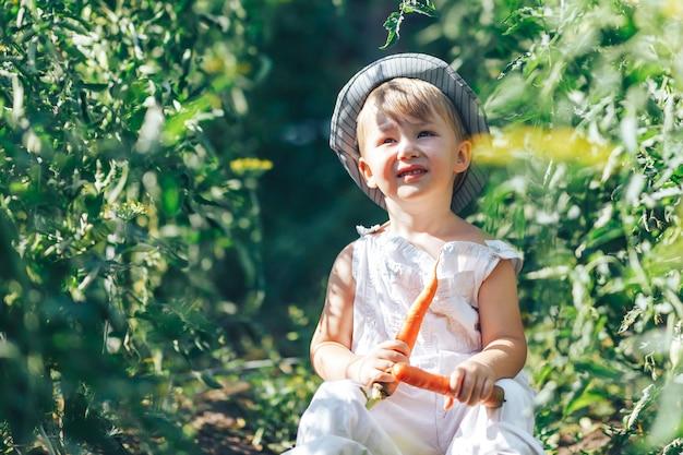 Bébé agriculteur avec carottes et clother cacual assis dans l'herbe verte