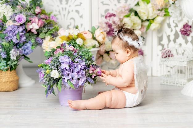 Bébé avec des ailes d'ange parmi les fleurs, le concept de la saint-valentin,