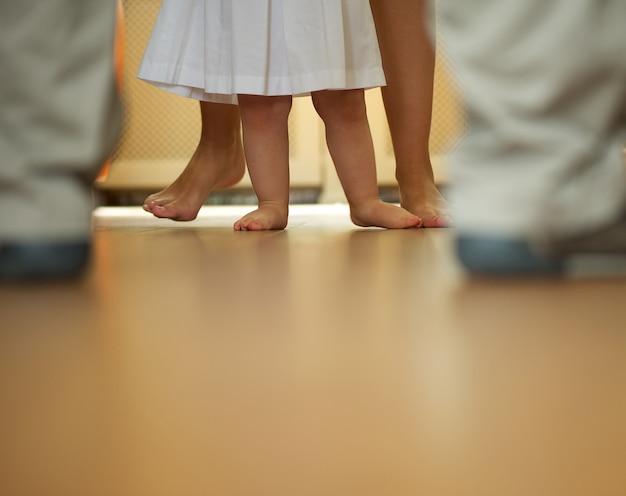 Bébé apprend à marcher avec l'aide de la mère et du père