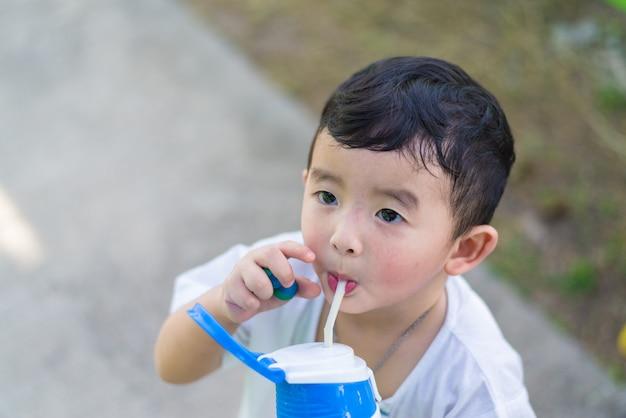 Bébé asiatique garçon l'eau potable avec de la paille.