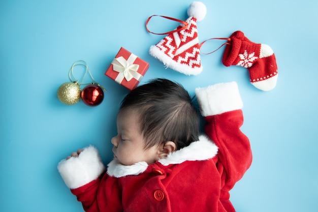 Bébé asiatique nouveau-né sur l'uniforme du père noël, dormant avec chapeau rouge et présent de boîte rouge sur fond bleu