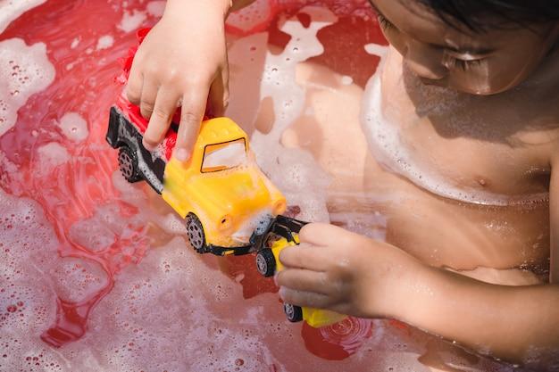 Bébé d'asie prenant un bain jouant avec des bulles de mousse et des jouets.