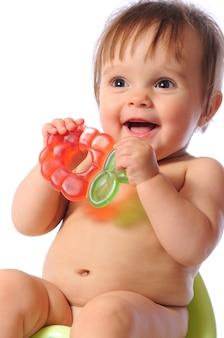 Un bébé assez heureux est assis sur un pot vert et tient un anneau de dentition dans les mains