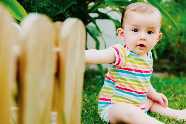 Bébé assis sur l'herbe aux pieds nus avec un sourire adorable.
