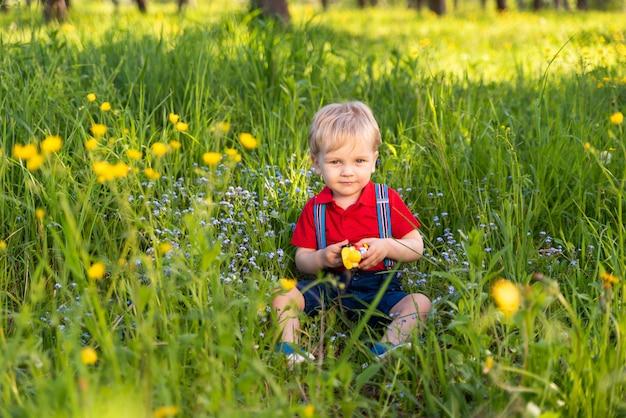 Bébé assis sur l'herbe avec un jouet dans ses mains