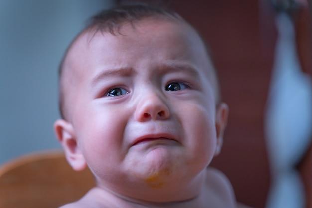 Bébé assis triste et pleurant dans la chambre
