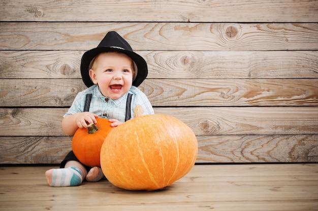 Bébé au chapeau noir avec des citrouilles sur bois