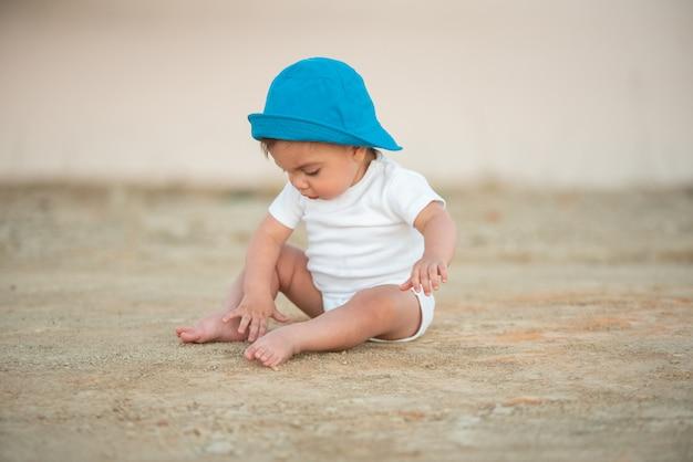 Bébé aux yeux bleus avec chapeau bleu assis sur le sol de sable