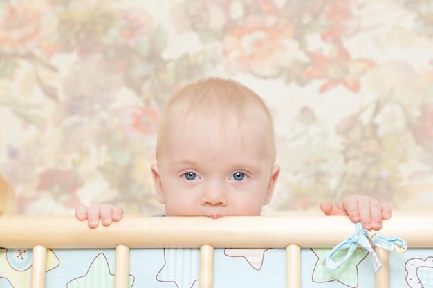 Un bébé aux yeux bleus dans un berceau