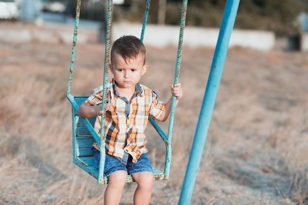 Bébé sur la balançoire se balançant près de la mer, en chemise et short en jean