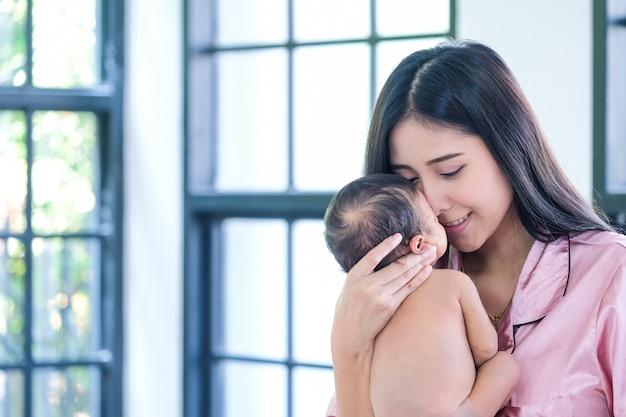 Un bébé en bas âge dans une tendre étreinte de la mère à la fenêtre