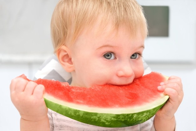 Bébé blond caucasien en train de déjeuner à la cuisine en mangeant des fruits frais sains de melon d'eau pour enfant