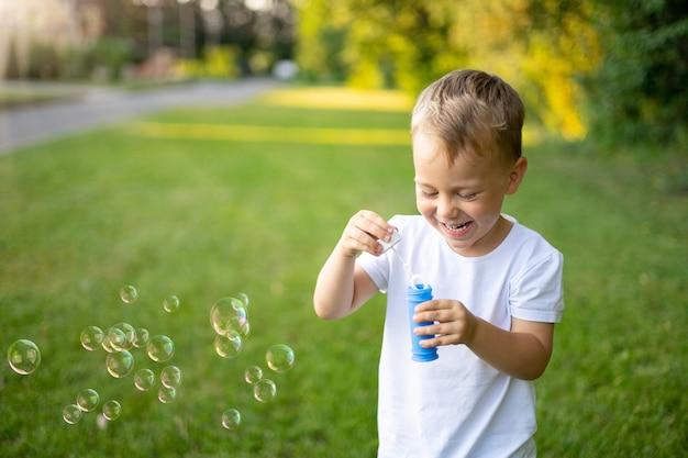 Le bébé blond mignon gonfle des bulles de savon en été sur une pelouse verte, s'amusant, loisirs de plein air
