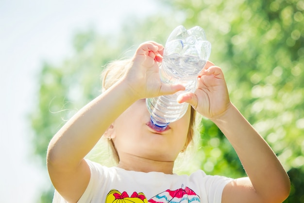 Bébé boit de l'eau de la bouteille. mise au point sélective.